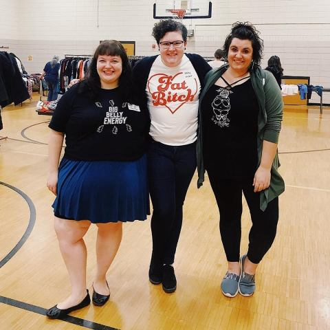 Three fat women stand next to each other smiling.